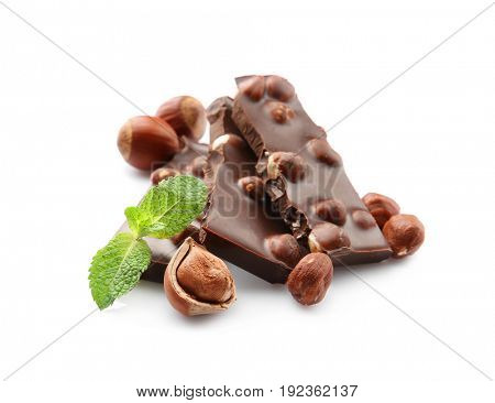 Broken chocolate pieces with nuts and mint leaves, isolated on white