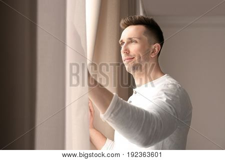 Man opening curtains in light room