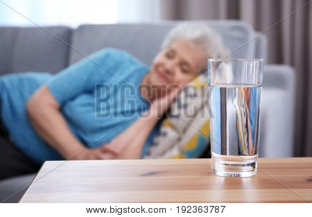 Glass of water on table and sleeping elderly woman at home. Concept of retirement