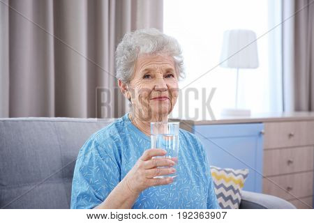 Elderly woman sitting on couch and holding glass of water. Concept of retirement