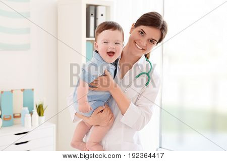 Female doctor and cute little baby in clinic. Baby health concept