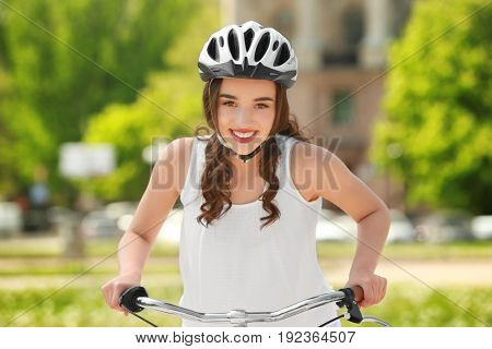Beautiful young woman riding bicycle in park on sunny day