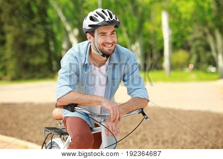 Handsome young man with bicycle and helmet in park on sunny day