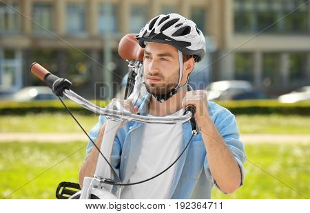 Sporty young man carrying bicycle outdoors