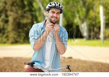 Handsome young man putting on bicycle helmet in park