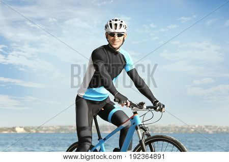 Sporty cyclist riding bicycle near river