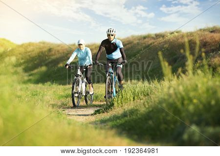 Sporty cyclists riding bicycles in countryside