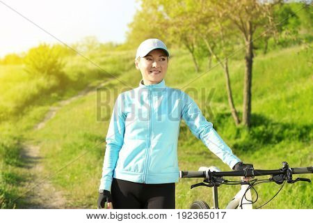 Beautiful young cyclist with bicycle outdoors