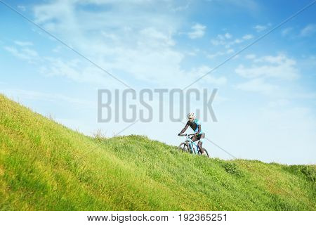Sporty cyclist riding bicycle in countryside