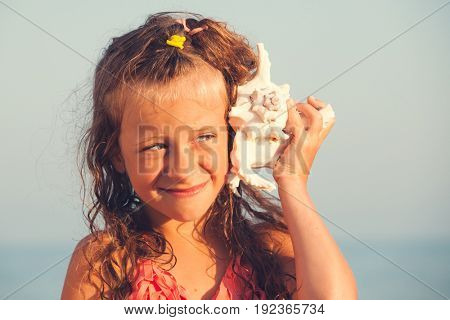 Child put the shell to her ear. Summer vacation. Girl on sea background