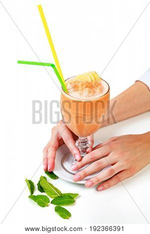 Closeup shot of banana smoothie in a big glass cup with two straws in woman's hands. Isolated on white background. Lady with a drink