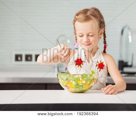 Little child eating vegetable salad in the kitchen. Child at home