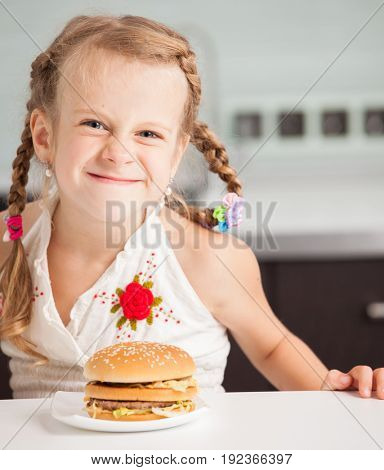 Child with hamburger at kitchen