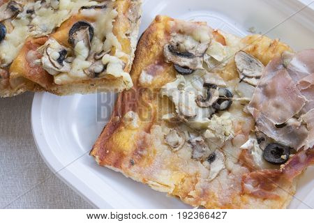 pieces of pizza with cooked ham black olives anf mushrooms