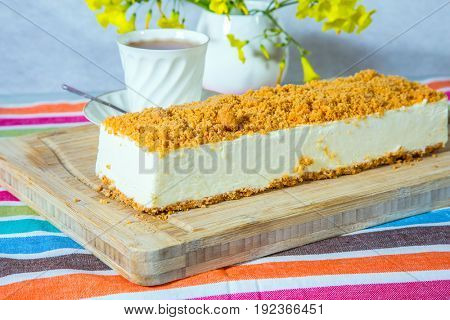 Gorgeous white cheesecake, sprinkled with sweet crumbs. The background is  vase with daisies and porcelain cup with hot tea. Professional bakery