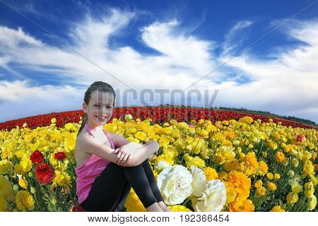 Charming smiling girl with a scythe in the kibbutz field of blooming yellow and red buttercups