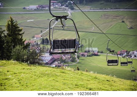 Cable way in German Alps - spring rural fields in the background