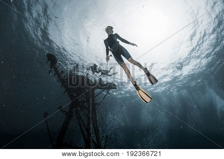 Woman freediver dives deep underwater along the ship wreck