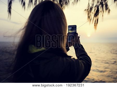 Woman taking photo on the beach