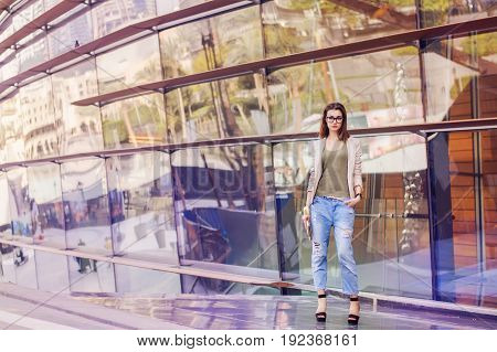 Young woman with bob hair cut eyeglasses in beige jacket and boyfriend jeans standing near glass building. Street fashion. Smart casual