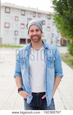 Casual guy with a denim shirt relaxed in the street