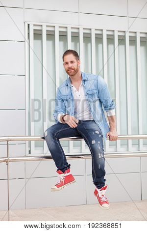 Casual guy with denim clothes sitting on a railing in the street