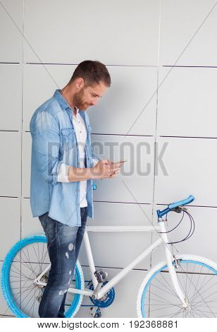 Casual guy next to a vintage bicycle with the mobile wearing denim shirt