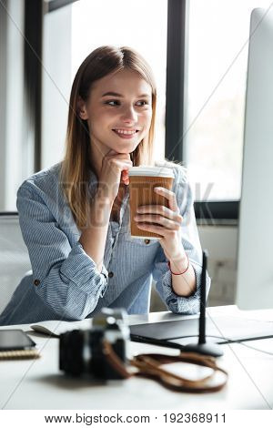 Image of smiling young woman work in office using computer and drinking coffee. Looking aside.