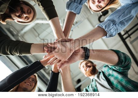 Image of young colleagues in office holding hands of each other. Looking aside.