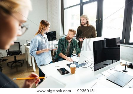 Image of young concentrated colleagues in office using computer. Looking aside.