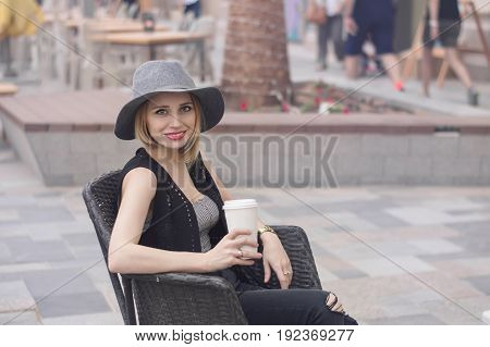 Portrait of young blond woman with bob cut hairstyle grey hat red lips and trendy jeans sitting outside and drinking coffee. Smiling and positive female with cappuccino
