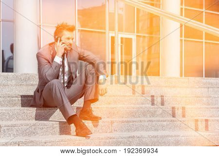 Full length of young businessman answering cell phone on steps outside office