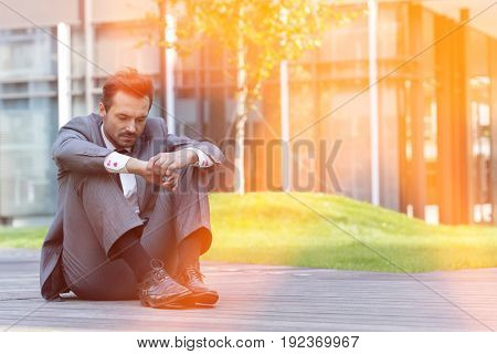 Full length of sad businessman sitting on path outside office