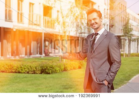 Portrait of confident real estate agent presenting office building