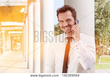 Portrait of happy young businessman using mobile phone outside office