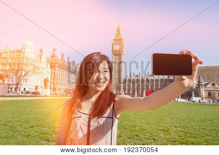 Young woman taking self portrait through smart phone against Big Ben at London; England; UK