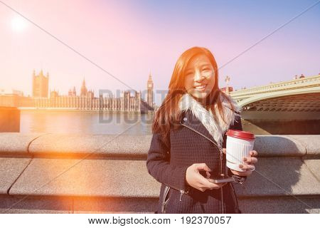 Portrait of happy young woman holding cell phone and disposable cup against Big Ben at London; England; UK