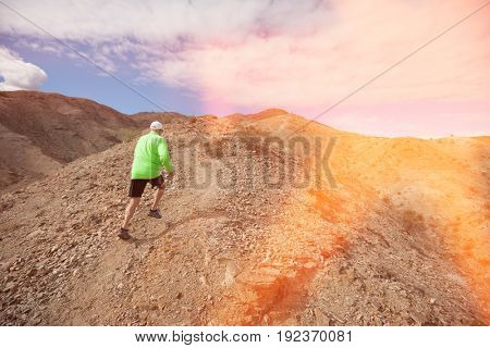 Rear view of senior man jogging on mountain