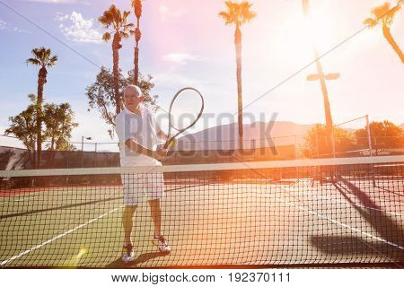 Senior male tennis player holding racket on court