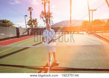 Portrait of senior tennis player offering handshake on court