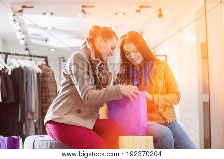 Young woman with friend looking into shopping bag at store