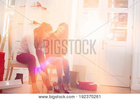 Young woman looking at friend trying on footwear in store