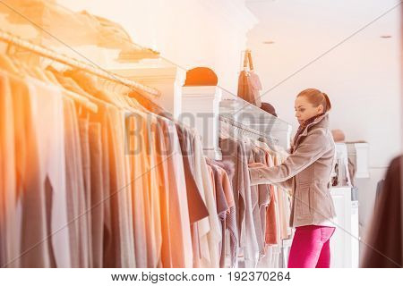 Side view of woman choosing sweater in store