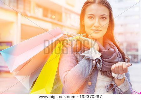 Woman carrying shopping bags while looking away