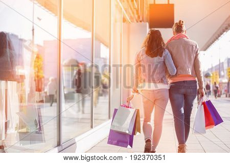 Rear view of young female friends with shopping bags walking on sidewalk by store