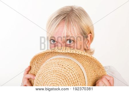 portrait of a attractive blond haired mid aged european woman wearing white dress hiding part of her face behind a summer head - headshot - studio shot on white background.