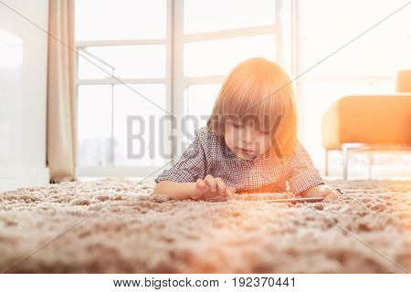 Boy using digital tablet while lying on rug in living room