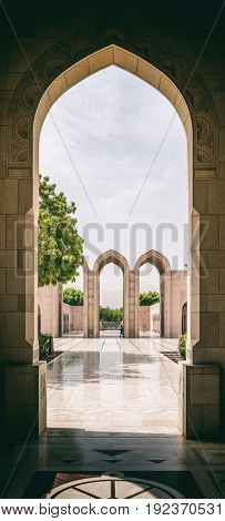 MUSCAT, OMAN - CIRCA AUGUST 2016: IArched stone entry way leading to courtyard with tree on a sunny afternoon