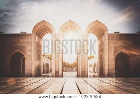 MUSCAT, OMAN - CIRCA AUGUST 2016: Inspirational image of stone arched entry way with reflective courtyard as the glaring sun shines behind it