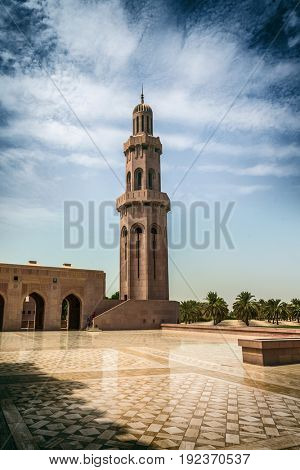 MUSCAT, OMAN - CIRCA AUGUST 2016: ISolitary tall stone minaret with domed top with dramatic clouds overhead
